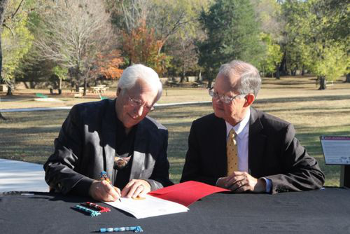 Cherokee Nation Principal Chief Bill John Baker and Dr. Bob Blackburn, executive director of the Oklahoma Historical Society, sign the official certificate of transfer for Sequoyah's Cabin near Sallisaw, Oklahoma, on Nov. 9, 2016